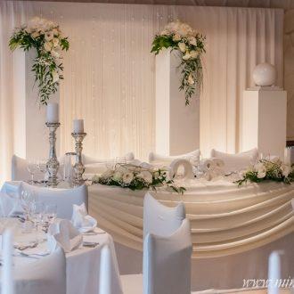 Brauttisch mit Hintergrund. Weisse Säulen mit 2 Blumengestecken und 2 weißen Kugeln, 2 Brauttischgestecken und 4 bauernsilberne Kerzenständer