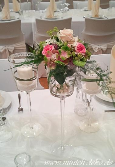 Stielgläser mit Blumen und Kerzen